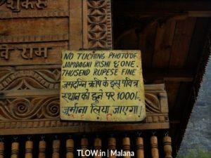 warning board on the temple in malana